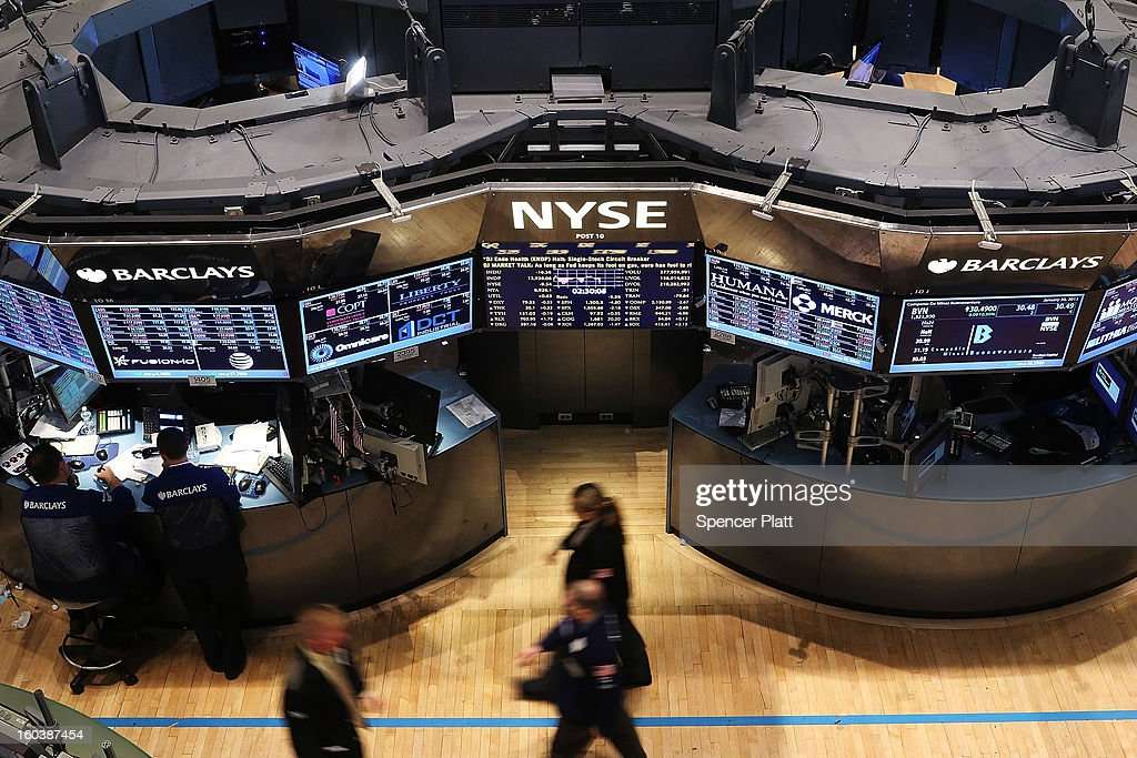 Traders work on the floor of the New York Stock Exchange moments after the Federal Reserve announced they will make no major changes to their...
