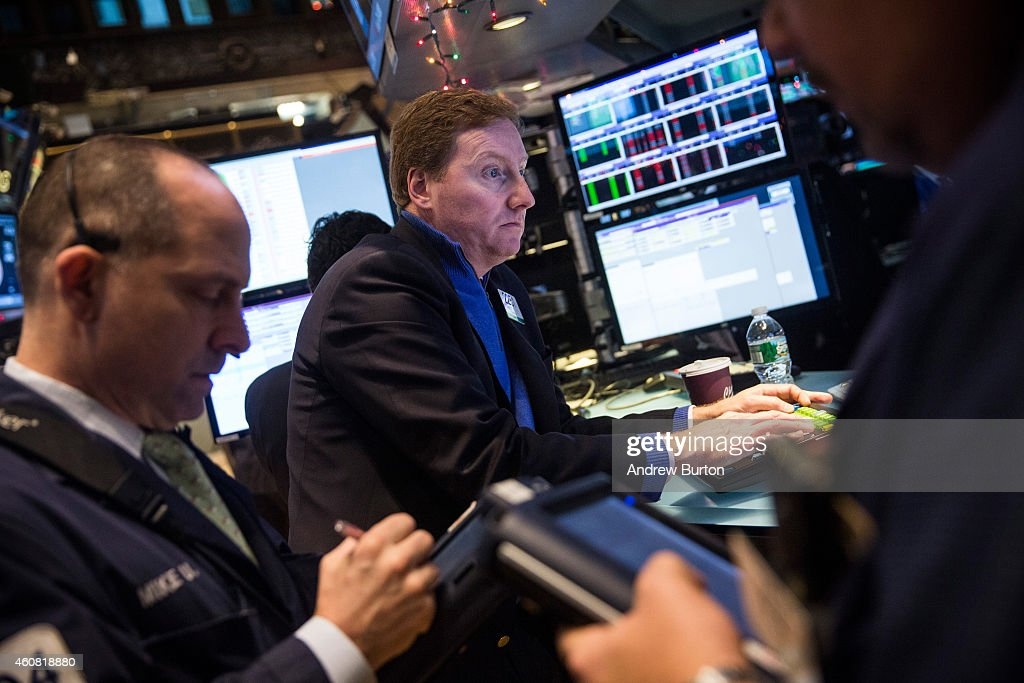 Traders work on the floor of the New York Stock Exchange on the morning of December 24 2014 in New York City The market opened above 18000 points for...