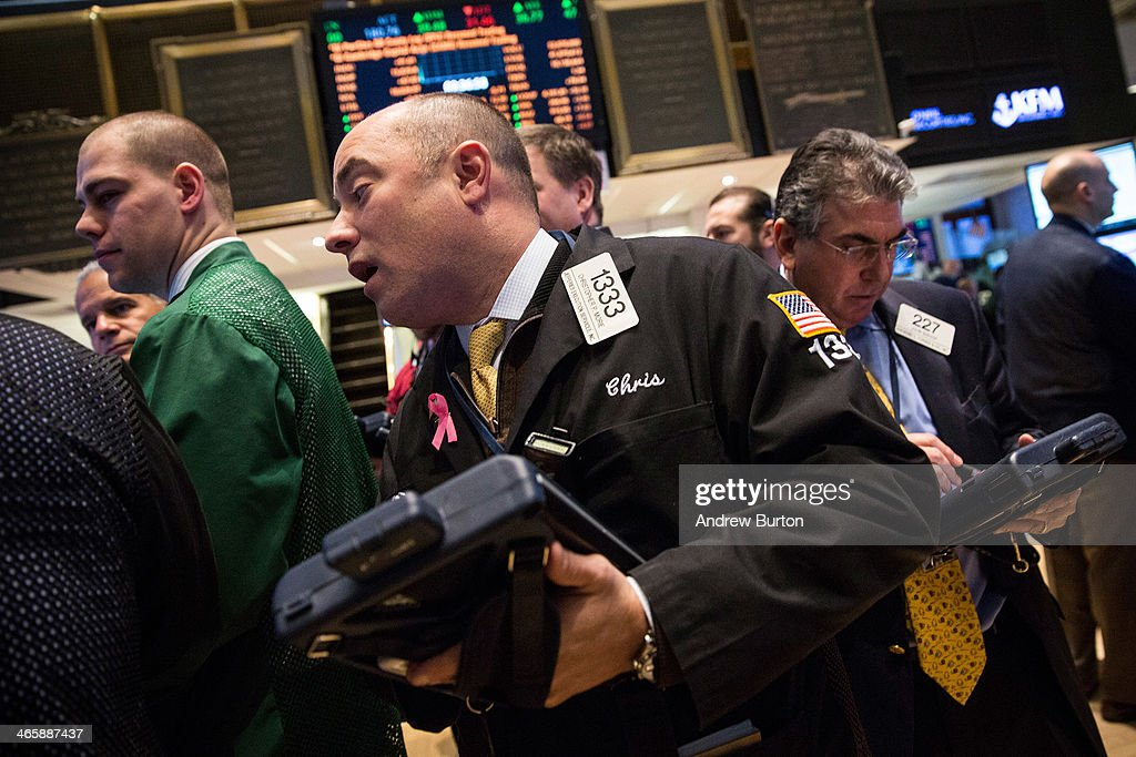 Traders work on the floor of the New York Stock Exchange (NYSE) on the morning of January 30, 2014 in New York City. The NYSE welcomed members of the Super Bowl Host Committee, owners and managers of the Denver Broncos and Seattle Seahawks to ring the opening bell today.