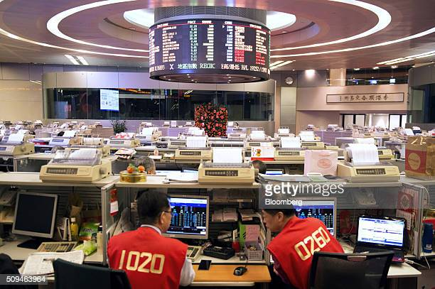 Traders work on the trading floor of the Hong Kong Stock Exchange operated by Hong Kong Exchanges and Clearing Ltd during the first day of trading...
