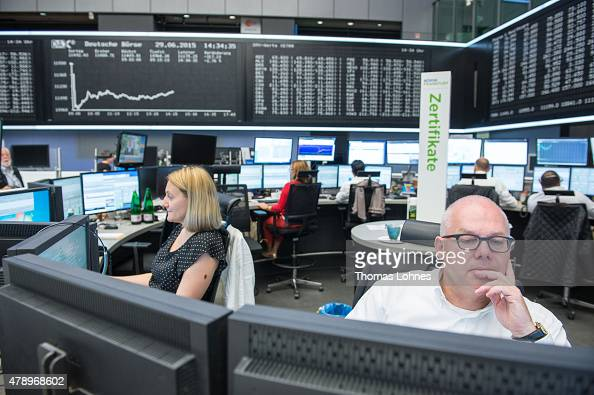 Traders work under the day's performance graph showing a sharp drop of the German DAX stock market index early today and a partial recovery later on...