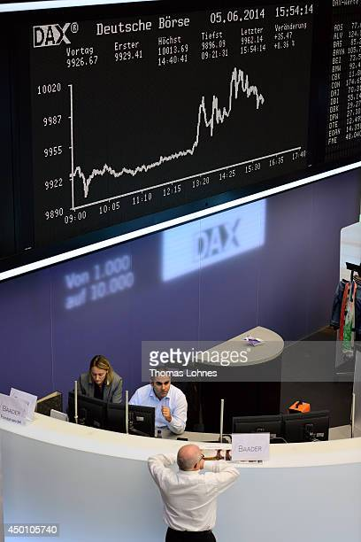 Traders work under the index board that shows the DAX has broken the 10000 mark for the first time ever at the Deutsche Boerse exchange on June 5...