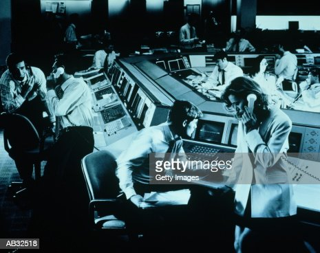 Traders working at terminals in dealing room (Blue Toned) : Stock Photo