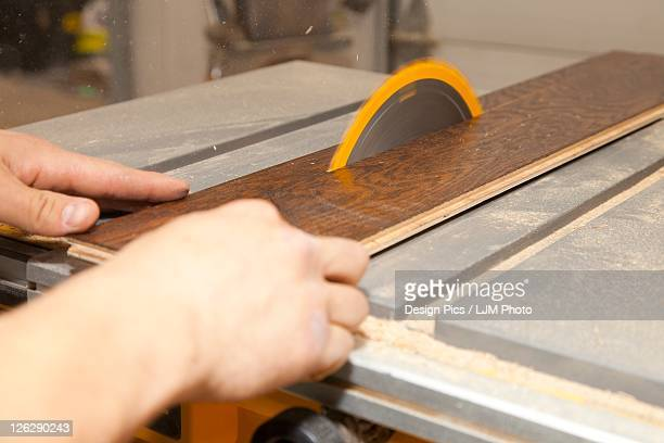 tradesman using a table saw to cut hardwood