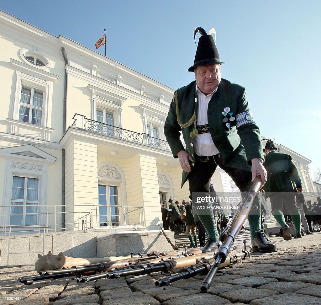 A tradionally dressed member of the Bavarian mountain troopers puts down his rifle prior to entering the presidential Bellevue Palace in Berlin, Germany on March 13, 2013.