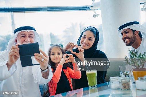 Familia tomando autofoto estilo tradicional árabe en Café