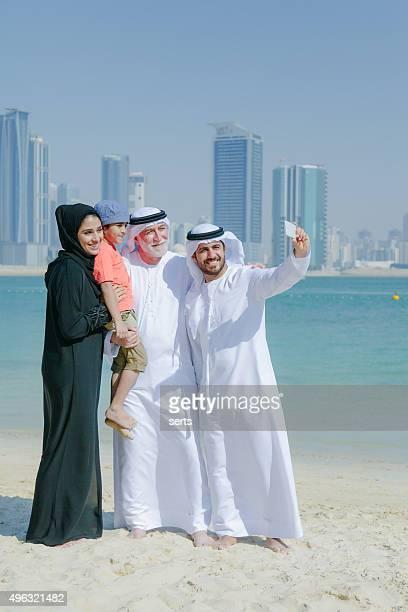 Traditional Arabian family taking selfie at park