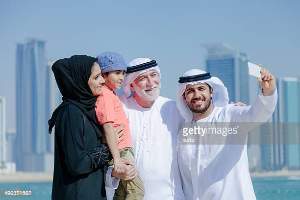 Traditional Arabian family taking selfie at park
