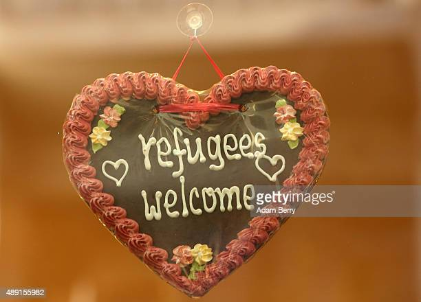 A traditional Bavarian Lebkuchenherz or heartshaped gingerbread cookie reading 'Refugees Welcome' hangs in a shop window on September 19 2015 in the...