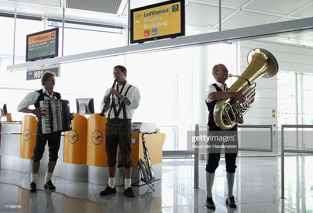Traditional Bavarian musicans greet the passengers in front of check in gate during a photocall for the Lufthansa cabin crew members in traditional 'Blaudruck Dirndl' dress on September 01, 2006 in Munich, Germany. From September 1 to October 3 Lufthansa cabin crew will dress in the Bavarian traditional costume.