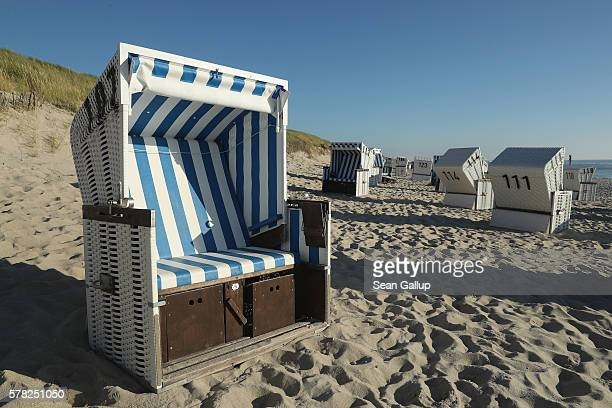 Traditional beach chairs that protect visitors from both sun and wind stand on a beach on the northern end of Sylt Island on July 19 2016 near List...