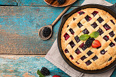 Homemade Traditional berry pie in a frying pan, sweet baked pastry food on rustic wooden table, top view