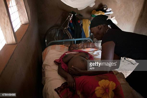 Traditional Birth Assistant Estelina Umbare examines the abdomen of a pregnant woman at her home in the village of Kuzee South Sudan on March 13 2014...