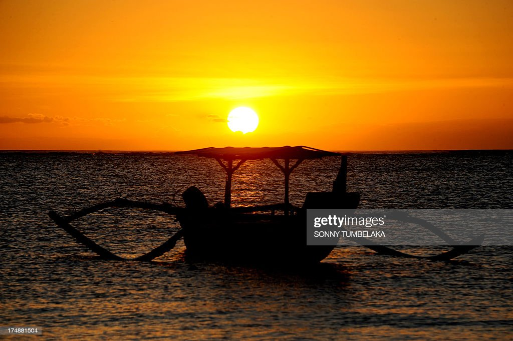 A traditional boat moors during sunset at a beach in the Kuta area of resort island Bali on July 29, 2013. The beauty of Bali allures thousands of tourists every month, making tourism the main income source for its residents.