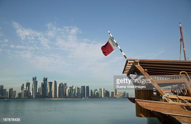 Traditional boat with Qatar's flag and Doha skylin