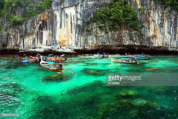 Traditional boats by cliffs, tropical green ocean