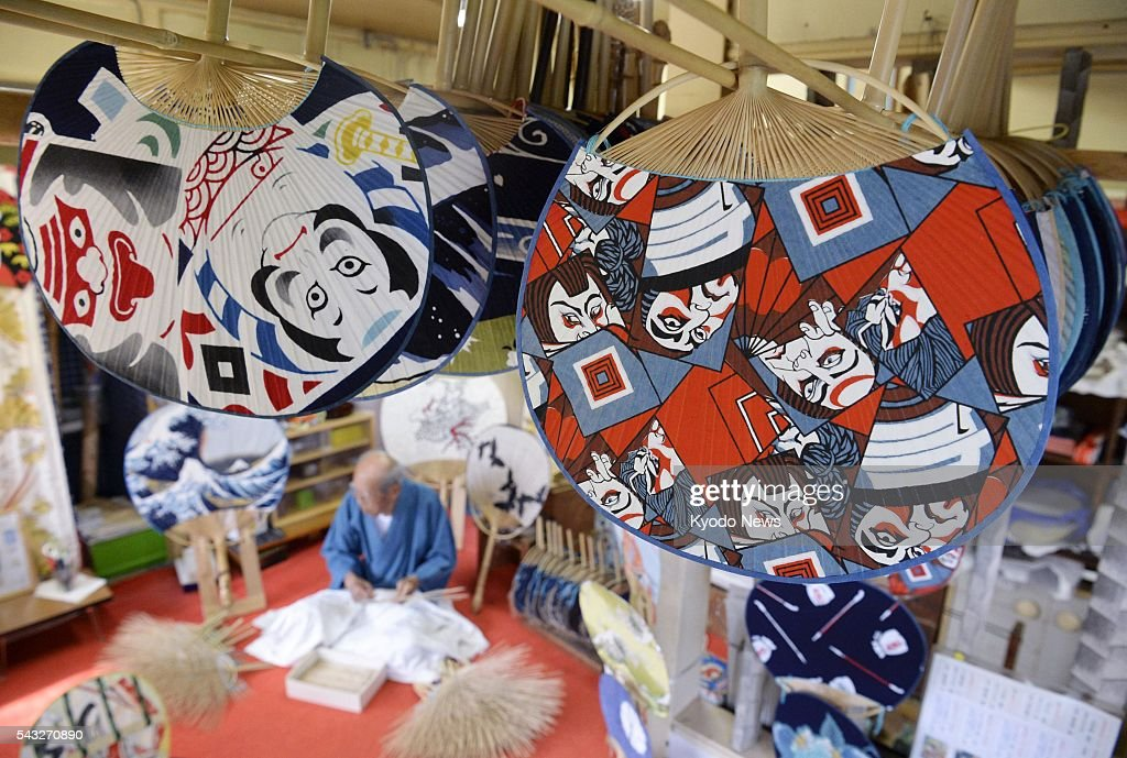 Traditional 'Boshu Uchiwa' fans created by 85-year-old Masao Uyama (background) are displayed at his studio in Minamiboso, near Tokyo, on June 27, 2016, ahead of Japan's hot and humid summer. The Boshu Uchiwa is one of three major uchiwa fans in Japan, along with those created in the former capital of Kyoto and the western city of Marugame. The prices of Boshu Uchiwa fans range from 1,000 yen to 30,000 yen.