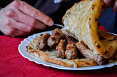 Closeup of traditional Balkan food- meat in bread/ man eating cevapi