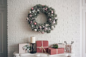 A traditional bright Christmas wreath hanging over the fireplace, on a white brick wall, and packaged gifts are stacked on a fireplace with candles. Christmas concept, new year.