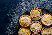 Traditional British Christmas Pastry Dessert Home Baked Mince Pies with Apple Raisins Nuts Filling Golden Shortcrust Powdered on Vintage Metal Plate Dark Blue Snowy Background Top View Copy Space