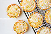Traditional British Christmas Pastry Dessert Home Baked Mince Pies with Apple Raisins Nuts Filling on Cooling Rack. Golden Shortcrust Powdered. White Plank Wood Table. Festive Setting