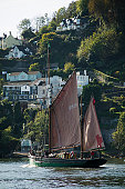 A traditional Brixham sailing trawler sailing out of the estuary of the River Dart, with Dartmouth in the background, Devon, Great Britain.