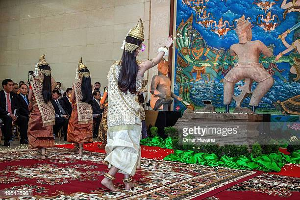 A traditional Cambodian Apsara dancer throws lotus petals to the Duryodhana statue during a ceremony to handover three statues back to Cambodia at...