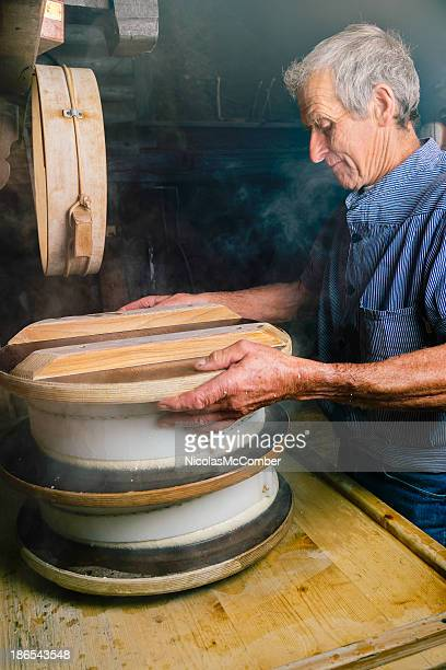 Traditional cheese maker places weight on fresh wheels