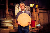 traditional cheesemaking - farmer holding wheel of cheese