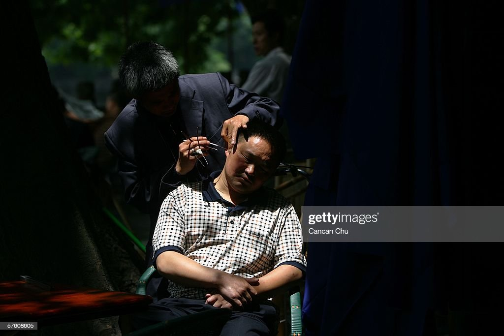 A traditional Chinese ear cleaner performs a cleaning service for a client at a tea house on May 14, 2006 in Chengdu, Sichuan Province of China. Cleaners with a handful of metal tweezers, tongs, feathered sticks and bamboo scoopers roam parks and street corners to offer their service for about 4-10 yuan ($0.5-1.25) for a quick five-minute clean.