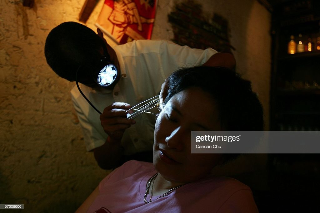 A traditional Chinese ear cleaner wears a headlight as he performs a cleaning service for a client at a tea house on May 14, 2006 in Chengdu, Sichuan Province of China. Cleaners with a handful of metal tweezers, tongs, feathered sticks and bamboo scoopers roam parks and street corners to offer their service for about 4-10 yuan ($0.5-1.25) for a quick five-minute clean.