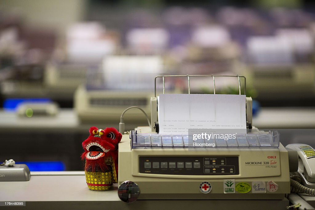 A traditional Chinese lion-dance figurine sits next to a dot matrix printer on a trader's desk at the Hong Kong Stock Exchange in Hong Kong, China, on Tuesday, Aug. 13, 2013. Hong Kong Exchanges & Clearing Ltd., operator of the Hong Kong Stock Exchange, is scheduled to release second-quarter results tomorrow. Photographer: Jerome Favre/Bloomberg via Getty Images
