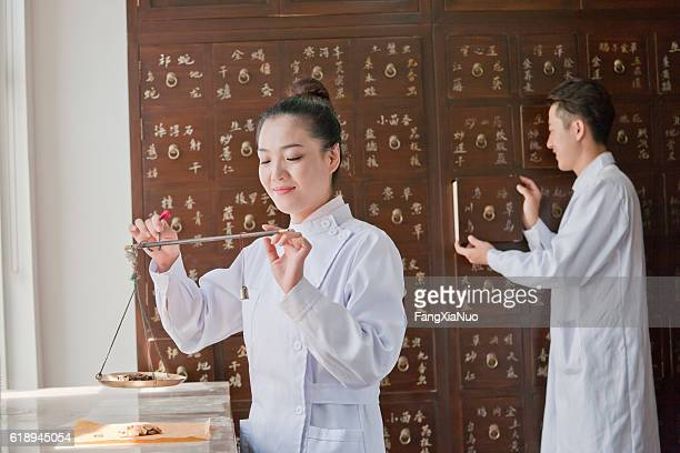 Traditional Chinese medicine doctor weighting medicine on scale