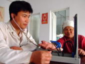 A traditional Chinese medicine physician checks the blood pressure of an elderly patient at the only clinic of a rural village in Baotou China's...