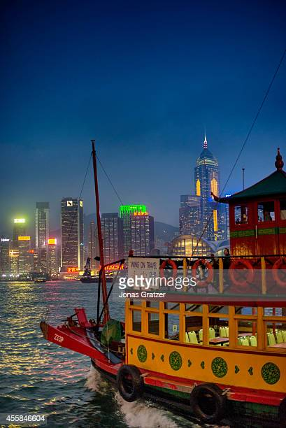 A traditional Chinese style passenger boat on the river with the backdrop of the city skyscrapers and highrise buildings lit up in the evening light...