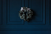 traditional christmas decoration evergreen wreath with white flowers ribbon on dark blue wall background.