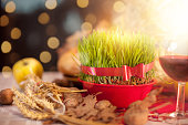 Traditional Christmas decoration with Christmas wheat, Yule log and wine