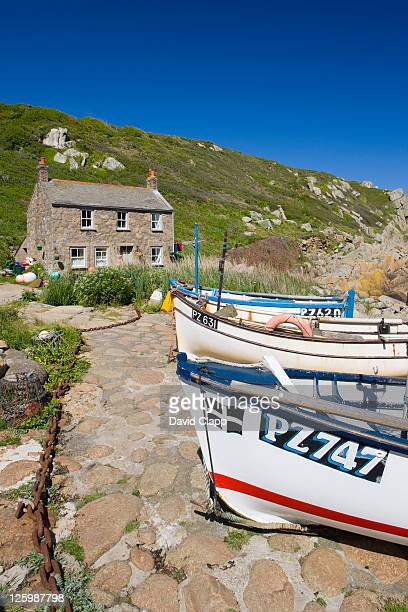 Traditional cottage and crab potting boats moored near water's edge at Penberth, Cornwall, England