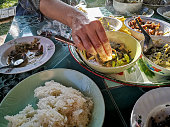 Traditional culture of eating by hand with small balls of sticky rice dipped in traditional Northern Thai curries and soups, this is the traditional way that, individuals and Thai families eat togethe