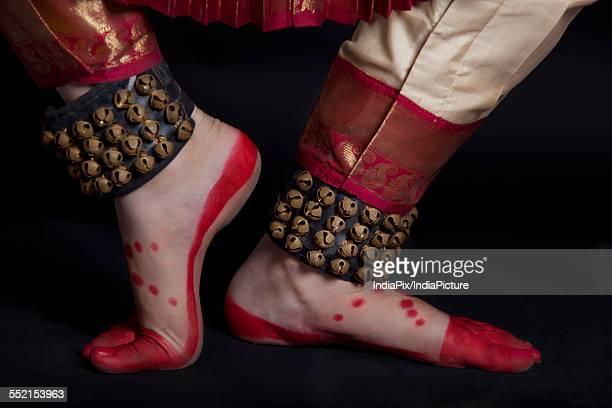 Traditional dancers feet performing Bharatanatyam against black background