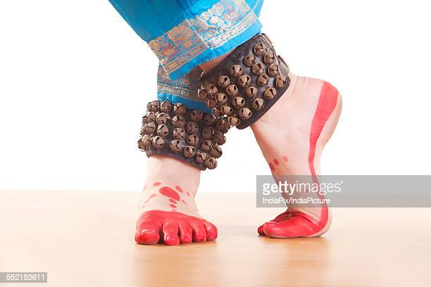 Traditional dancers feet performing Bharatanatyam against white background