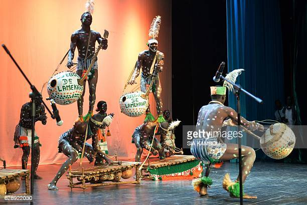 Traditional dancers perform during an international competition on December 9 2016 at the 'palais de la culture' in Abidjan / AFP / SIA KAMBOU