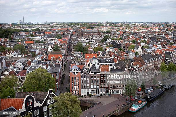 Traditional Dutch residential properties sit on a street as houseboats sit on the canal in Amsterdam Netherlands on Wednesday Aug 26 2015 Seven years...