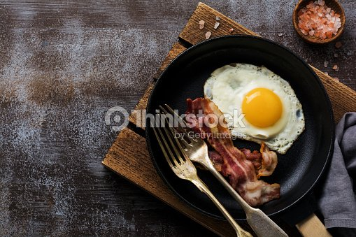 Traditional English breakfast with fried eggs and bacon in cast iron pan on dark concrete background. Top view. : Stock Photo