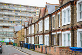 Traditional English terraced houses with huge council block in the background in south east London
