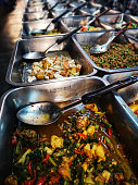 Traditional fast food Thai food trays with Thai dishes of curries and soups on display in a Thai food market. Customers choose what dishes they would like and then they are served with their choice, w