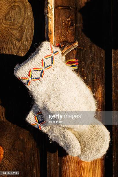 Traditional fingerless gloves hanging outside log cabin, close-up