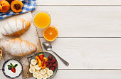 Traditional french breakfast menu background. Yogurt with fresh berries, glass of orange juice, fruit plate and croissants on wooden table, top view, copy space