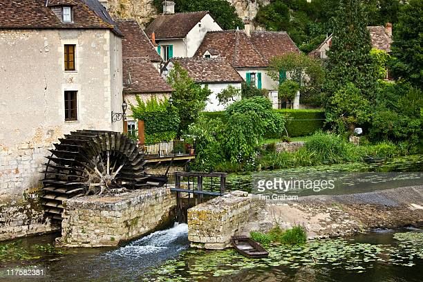 Traditional French houses water wheel and millrace at Angles Sur L'Anglin medieval village Vienne near Poitiers France