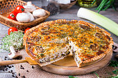 Traditional french quiche pie with chicken and mushroom on the table